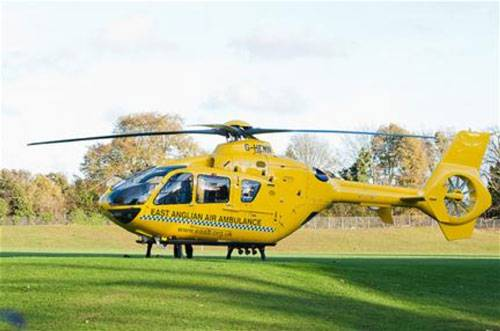 Yellow east anglian air ambulance landed on grass